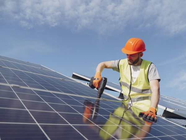 man-fixing-solar-panels-with-professional-drill-4254165